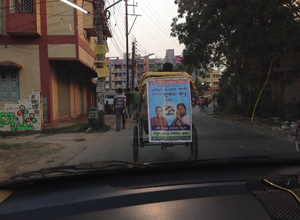 A rickshaw carries a campaign poster.